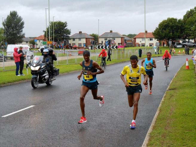 Mo Farah, Haile Gebrselassie, and eventual winner Kenenisa Bekele sprint past my mum at mile 8
